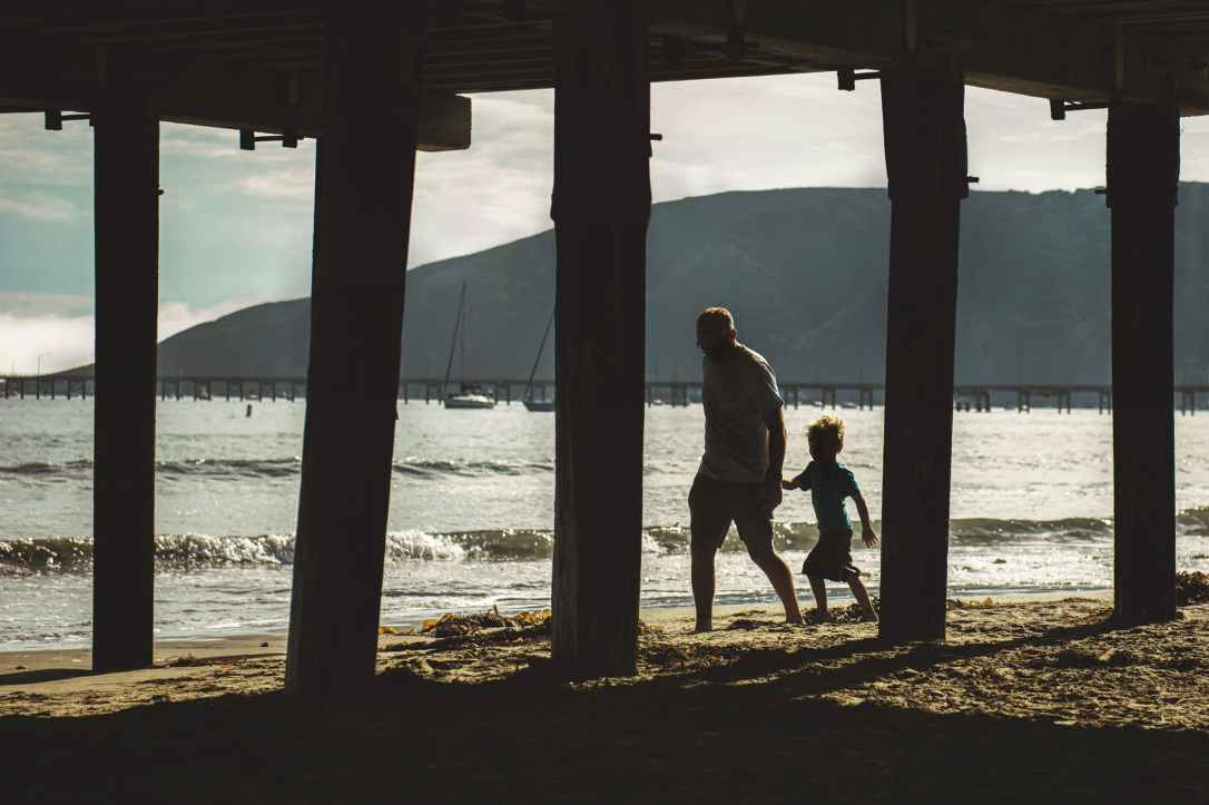 man and child walking on shore